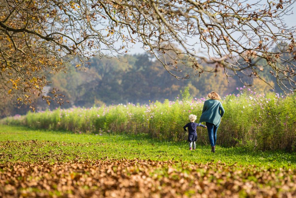 Moeder met kind wandelt in herfst in Rivierenland